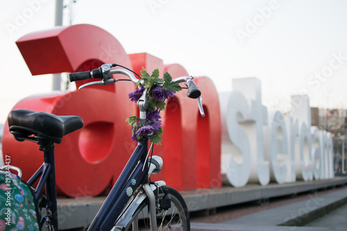 Fotobehang Fiets Amsterdam, The Netherlands, February 15th, 2018: A bicycle parked in front of the I Amsterdam sign
