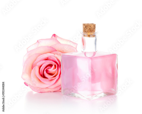 Pink rose and glass bottle with transparent liquid