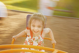 little girl spinning on a children's carousel among the playground. - 193368227