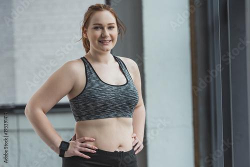 Sticker Curvy girl standing by window in gym
