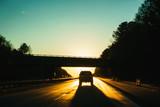 SUV driving into the sunset, sun hidden by bridge - 193406841