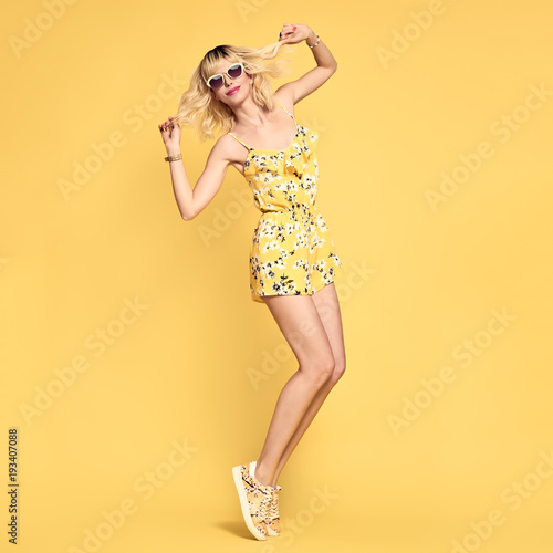 Short-haired girl in Fashionable Sunglasses Dancing. Young Playful female Blond model in Stylish fashion Summer Outfit. Beautiful Hipster woman Having Fun dance in Studio on Yellow