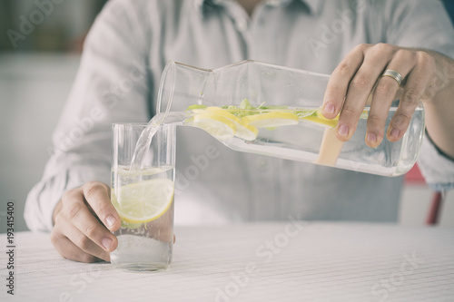 Fototapeta Young man pouring water from bottle to water in kitchen