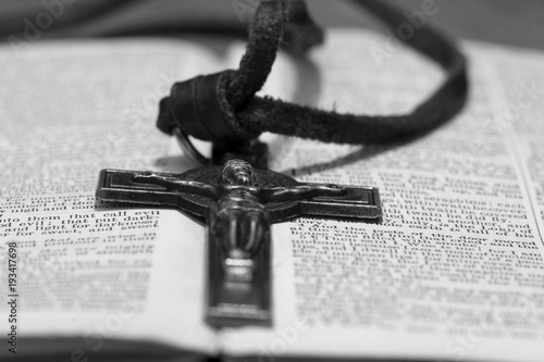 Crucifix necklace on a bible page with wood background in black and white