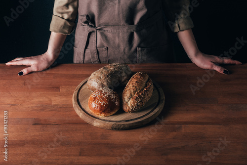 Wall mural partial view of woman standing at table with loafs of bread on wooden cutting board