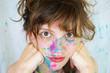 Mujer joven con manchas de pintura de colores en la cara