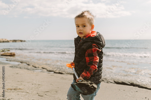 Foto op Plexiglas Cyprus baby boy on the beach in winter time playing with sand