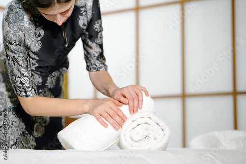 Foto op Plexiglas Spa The girl folds a towel, prepares a workplace in the spa for the reception of clients. The maid is preparing a room for the spa salon. Woman masseuse in the workplace. The concept of health and beauty.