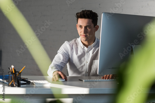 smiling thoughtful businessman sitting at workplace in modern office