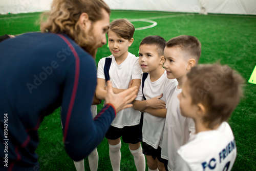 Young football trainer talking to team of little players on the field during break between games