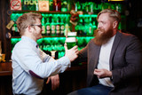 Two young irish men sitting in pub and toasting while having beer - 193441609