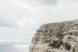 Small figure of traveler standing on edge of cliff. - 193442081