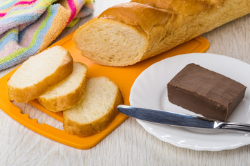 Pieces of bread on cutting board, napkin, chocolate butter, knife