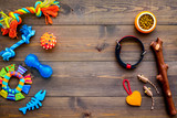 Pet accessories. Toys near bowls with animal feed, collar on dark wooden background top view copy space - 193444833
