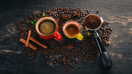 Two fragrant hot cup of coffee. Cinnamon. On a black wooden background. Top view. Copy space.