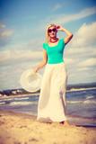 Blonde woman wearing dress walking on beach - 193467663