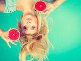 Woman holding red grapefruit having crazy windblown hair