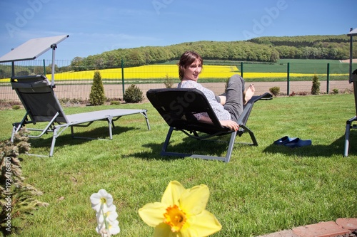 Staande foto Geel woman relaxing on a sun lounger with some hills and a rapeseed field in the background
