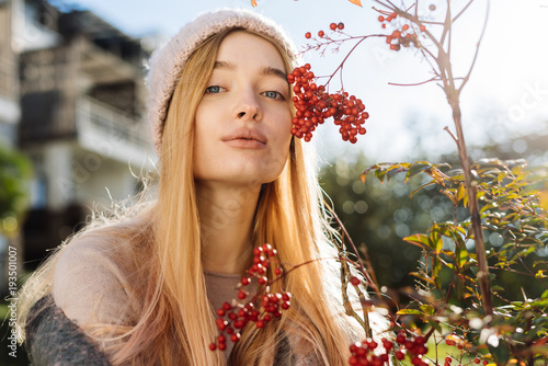 Fototapeta beautiful young blond girl in hat walking in the garden, enjoying the sun and nature, smiling