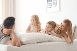 Happy family on bed with soft pillows at home