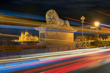 Lion statue on Budapest Chain bridge against Parliament building through bright traffic motion lights