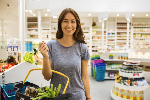 Pretty young woman in the modern food supermarket, with her basket. Face camera