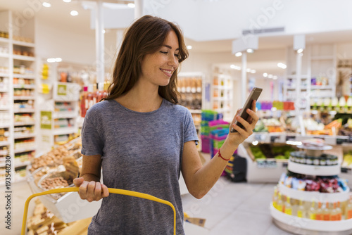 Casual cute female, using her mobile phone in modern market.