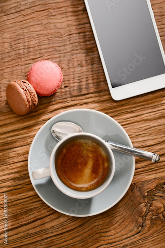 Sticker stylish still life above view with espresso coffee macaroons and french pastries on a rustic wooden tables with a smartphone