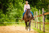 Cowgirl doing horse riding on countryside meadow - 193572277