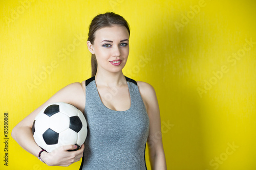 Fotobehang Voetbal Girl with a soccer ball on a yellow background. A beautiful girl in a gray sports suit smiles and holds a football ball.