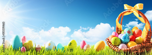 Papiers peints Herbe Easter Eggs in a Basket on Green Grass and Blue Sunny Sky