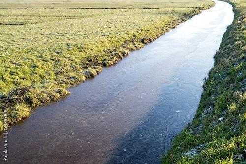 Foto op Plexiglas Beige half frozen drainage canal in Dutch acreage landscape