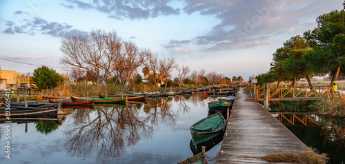 Albufera nature reserve with wooden fishing boats and pier at dusk