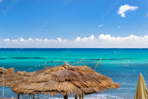 Tuinposter Bali Thatched umbrellas on the beach cafe. Bali, Crete