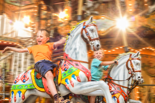 Foto op Aluminium Amusementspark begeisterte Kinder auf einem Karussell mit Pferden