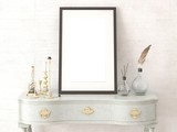 Mock up empty frame with stylish candlesticks and a fashionable chest of drawers.