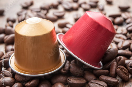 Fotobehang Koffiebonen dosette de café expresso avec grains de café sur table en bois