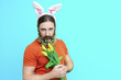 canvas print picture - Happy Easter concept. Nice kind muscle man male with flower's beard, white ears of rabbit and yellow spring's tulips isolated on blue background. Spring concept.