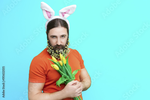 canvas print picture Happy Easter concept. Nice kind muscle man male with flower's beard, white ears of rabbit and yellow spring's tulips isolated on blue background. Spring concept.