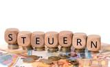 Steuern / Geld und Holzwürfel mit dem Wort Steuern