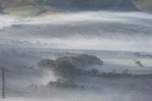 Foto op Canvas Grijs Stunning foggy English rural landscape at sunrise in Winter with layers rolling through the fields