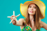Woman in yellow hat holding white shell - 193698005