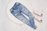Blue ragged  jeans and white sneakers on white fur. Fashionable concept - 193699823
