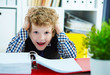 Small Caucasian curly boy grabbed his head while sitting over documents. Boy playing in the boss.