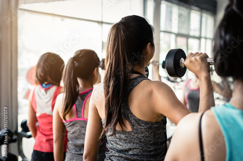 Fotobehang Fitness Group of woman lifting weights with dumbbells