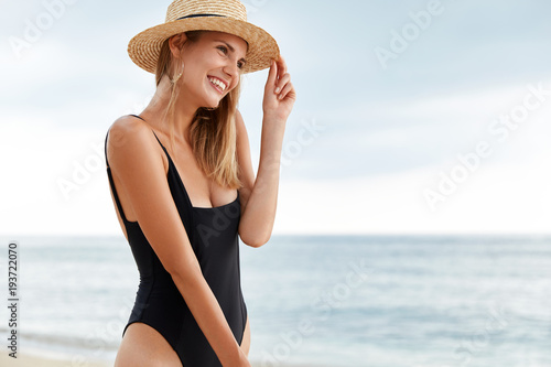Outdoor view of pleasant looking young female model in bikini and straw hat looks with dreamy expression away, enjoys beautiful ocean view and sunrise, spends summer holiday at beach in tropics