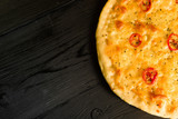 juicy pizza Margarita on a black wooden background - 193728453