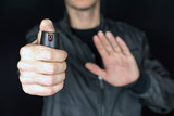 pepper gas in the hand of a young man in a black jacket CS spray self-defense Tear gas concept, close up, selective focus , blurred dark background - 193733469