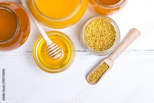 Honey in jar with honey dipper on wooden background © Pakhnyushchyy