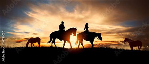 couple on horseback at sunset